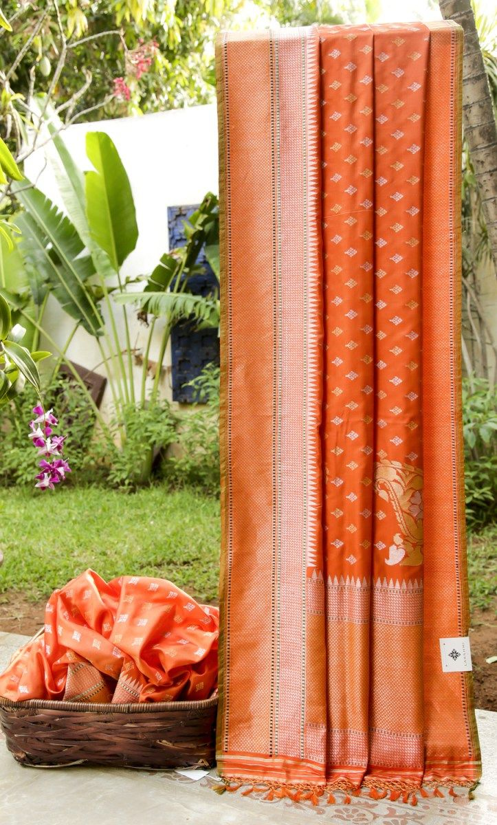 ORANGE BENARES SILK EMBELLISHED WITH ANTIQUE GOLD AND SILVER BHUTTAS ALL OVER. THE TEXTURED GOLD BORDER AND PALLU GIVE THE PIECE A CLASSIC FINISH