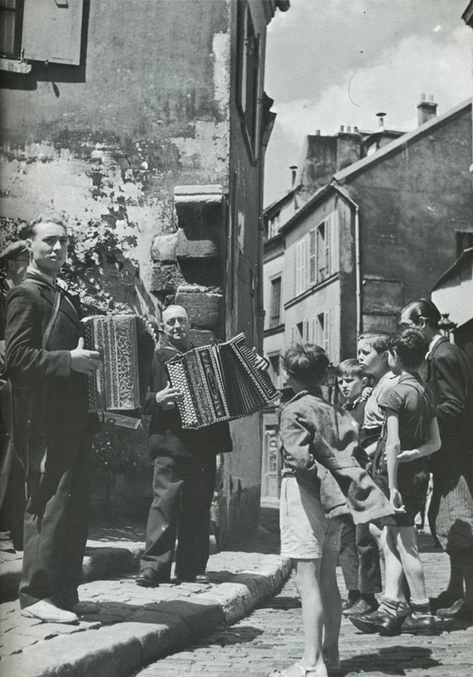 Quelques musiciens de rue dans le haut de la rue Norvins, tout près de la place du Tertre, sous l'oeil - et oreille - émerveillé des gosses de Montmartre, en 1930... (photo Roger Schall)