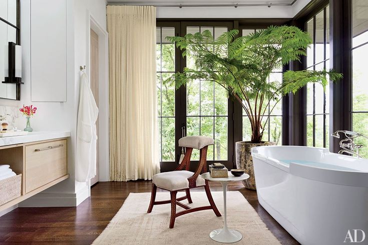 A bathroom in interior designer Ray Booth and John Shea's Nashville home is brightened up with a potted Australian tree fern next to the tub.  How to Add House Plants to Any Home Photos | Architectural Digest
