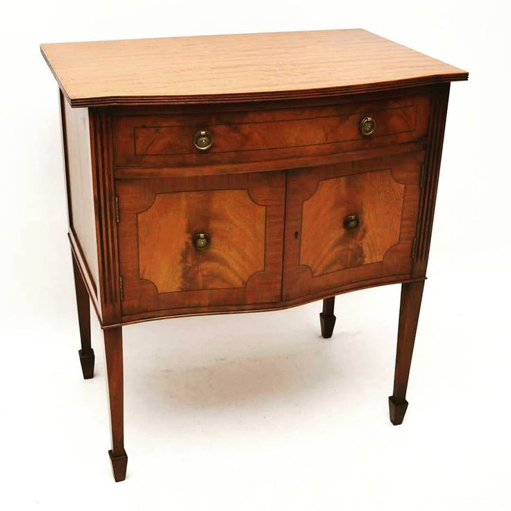Antique Inlaid Mahogany Cabinet on Legs at Marylebone Antiques | This is an antique mahogany cabinet with a serpentine shaped front sitting on square tapered spade end legs. Its a neat small size & almost like a small sideboard. Its mahogany with fame mahogany panels on the doors & on the drawer plus ebony inlays. The top edge is reeded & there is more reeding down the sides. This cabinet is in excellent condition& date from around the 1930s period. Contact us on…