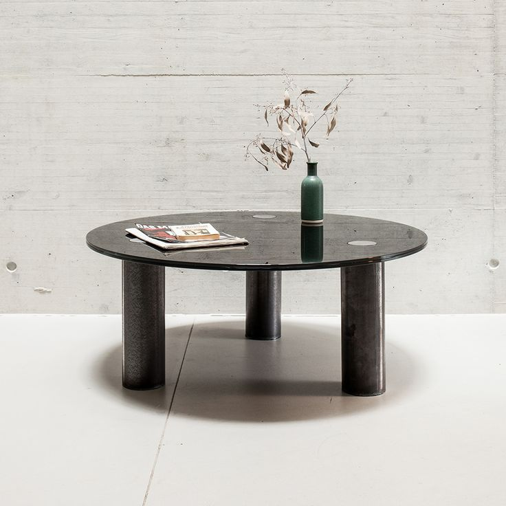 A Coffee table. The combination of geometric shapes that comprise this coffee table will add a modern touch to any living space.  The cylindrical, untreated steel legs provide a strong base for the circular black glass tabletop.  Artistic as well as sturdy and practical, this table has both a contemporary and timeless look.