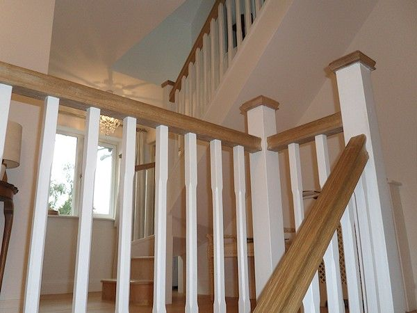 A softwood winder staircase for a loft conversion, painted white with feature oak handrail and newel caps.