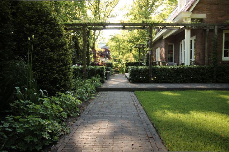 Deze dubbele pergola zorgt voor een verbinding tussen huis en tuin. Daarnaast geeft de transparante constructie veel diepte langs de zichtlijn. Klimrozen en blauwe regen zullen op termijn de hele pergola overgroeien.