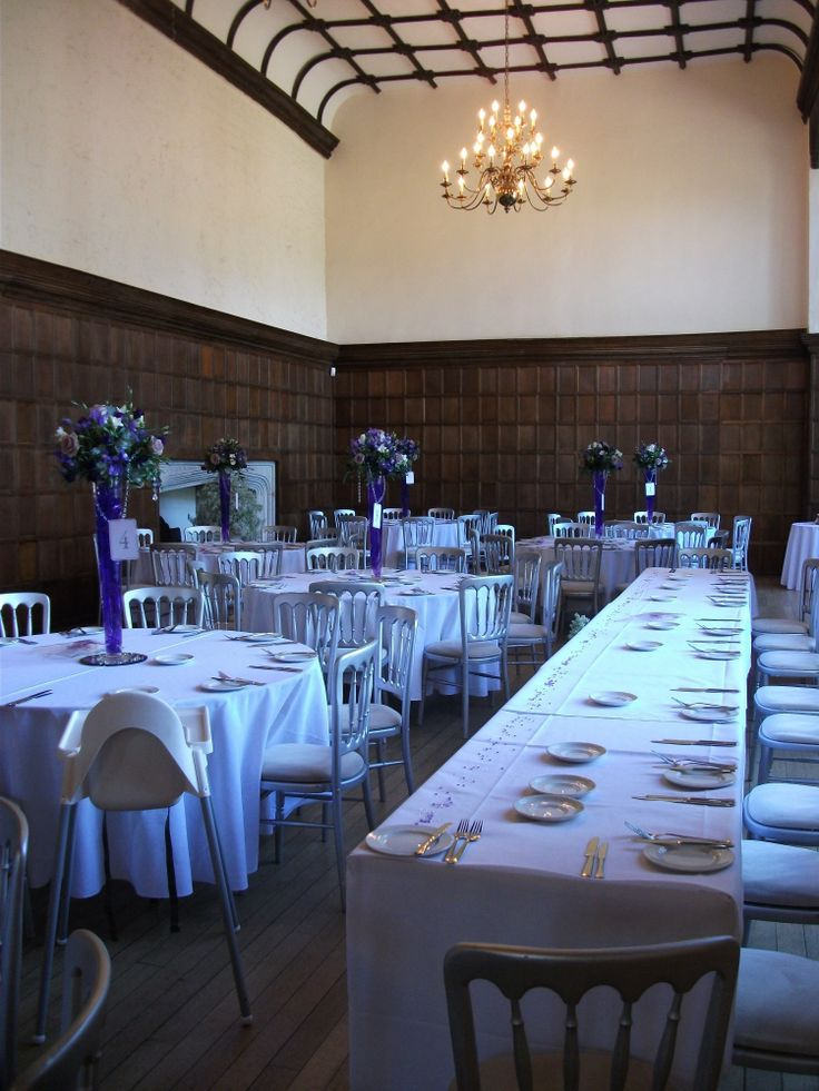 Purple tall vases, with crystals draped throughout to hang table names from.