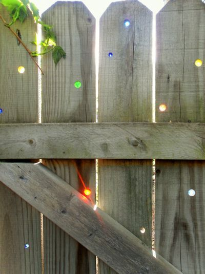 """"""" drilled holes into his backyard fence and inserted colored marbles to catch the sunlight and sparkle. Star constellations were his inspiration. I love this idea. Sometimes fences need bedazzling too."""""""