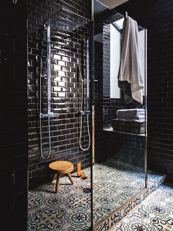 Plus sobre que le noir brillant des murs, les carreaux de ciment sont le chic de cette salle de bains
