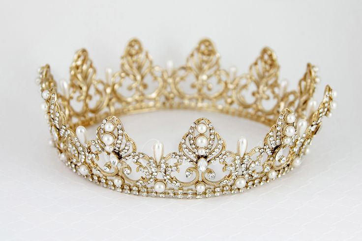 Make a glamorous statement with this royal, full circle bridal crown. Ivory teardrop pearls alternate with regal rhinestone covered designs set in antique silver. Surely this crown will complete your