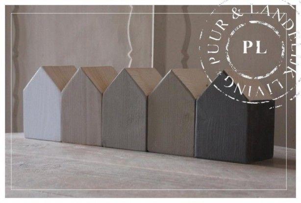 vierkante houten palen op maat afzagen, schuine daken eraf zagen en verven