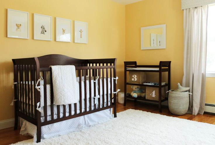 Banana yellow walls stand over natural hardwood flooring with thick shag white rug in this nursery. Dark wood crib and changing table stand under white framed animal paintings and mirror.