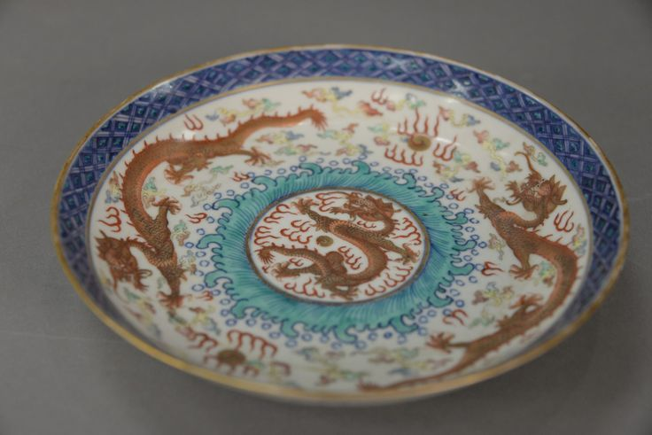 Chinese porcelain dragon dish having three enameled five claw dragons with flaming clouds and geometric blue border.