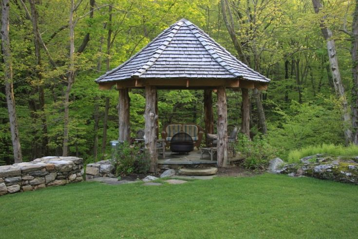 round gazebo with wood block poles, stone flooring, chairs, fire pit, shingles roof of The Exquisite Kind of Gazebo for Your House