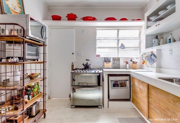 Cozinha clean com estante industrial, piso de cimento queimado e panelas le creuset.