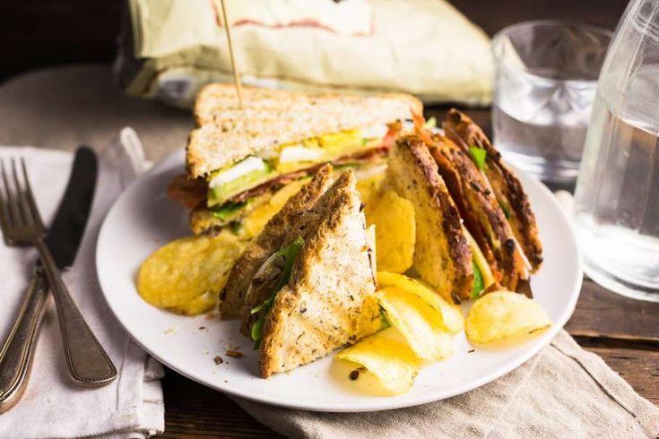 Recept voor luxe Club Sandwich voor 4 personen. Met zout, peper, satéprikkers, kaas, ham, brood, chips, ei, ontbijtspek, tomaat, sla, mosterd, mayonaise en komkommer