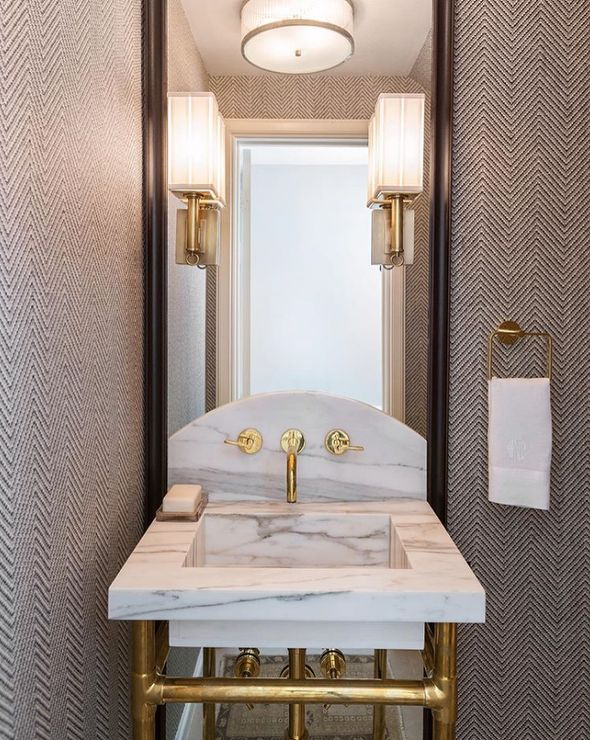 Beautifully appointed gray and gold powder room is clad in gray herringbone wallpaper and features two gold sconces mounted on a black vanity mirror above a brass and marble washstand finished with a brass faucet kit fixed to a curved marble backsplash.