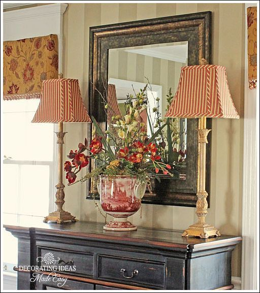 French Country Decorating: Red striped lamp shades and floral arrangement look cheery on the black console.