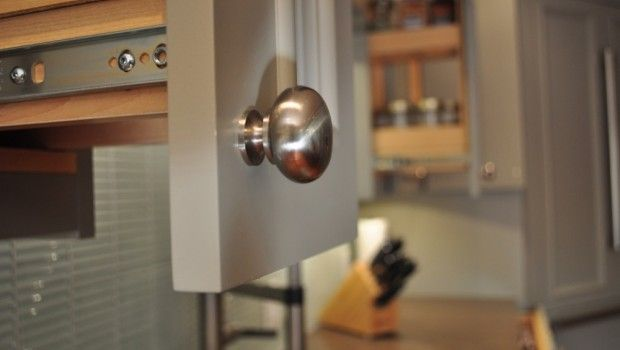 Brushed nickel knobs in this grey kitchen are both neutral and functional.