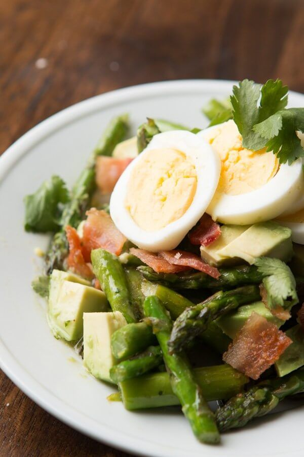 We cannot stop making this asparagus avocado salad! Hard boiled eggs, asparagus, bacon, avocado and the yummiest dressing!