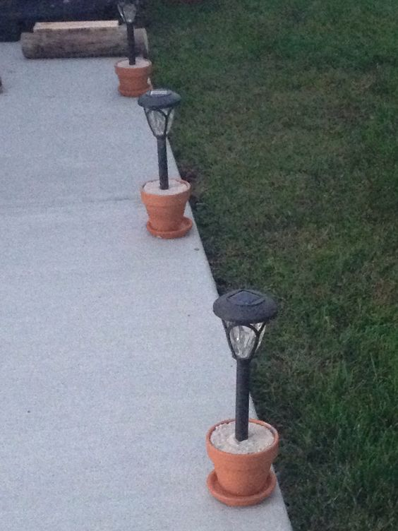 Problem: Solar lights staked in yard are difficult to mow & weed eat around. Solution: Terra cotta flower pots & a bag of quick-krete. Mix concrete according to the package directions. Scoop into flower pot & immediately put light into the center (remove the stake first). It sets quickly so do one at a time. Once finished, you have cute, functional & completely portable outdoor lights. (Note: you will only need about a quarter of a bag of quick-krete to fill 8 pots).