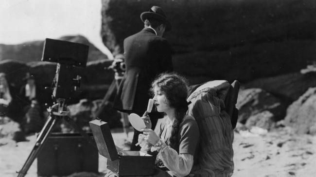 Mildred HARRIS [*] Mildred Harris, a leading lady and first wife of Charlie Chaplin, is applying make-up on the beach between production shoots. Pic: c.1923.