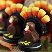 Thanksgiving Turkey Cookies --- Made from Oreo cookies, candy corn, malted milk balls, peanut butter cups, and frosting to hold it all together. Looks yummy!