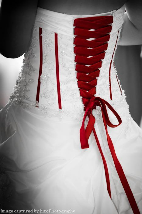 The back of a brides wedding dress with red lace up detail and a corset ribbon. Photographed by Jinx Photography, www.JinxPhotography.co.uk