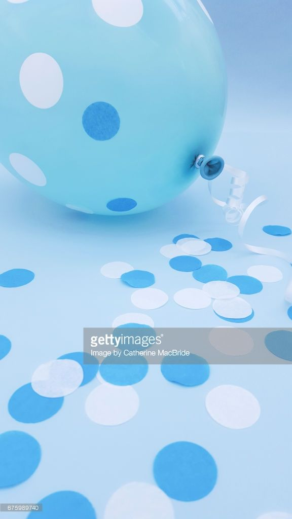 A blue balloon and blue and white circular confetti on a pastel blue background
