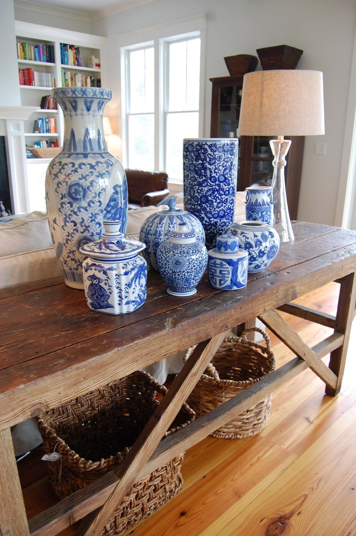 Ginger jars (some antique) mixed with vases from HomeGoods add a pop of color to this farmhouse table in a coastal home.