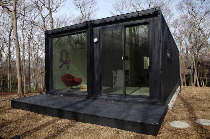 black shipping container home with glass walls