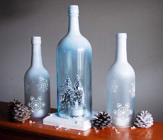 Se trata de un conjunto de mano helada y pintó botellas de vino transformados en sostenedores de vela del huracán. Las botellas han sido mano cortada y lijada a la perfección por lo que hay no hay bordes afilados. Tapas de las botellas están pintados de blancos y se descoloran abajo en un efecto helado helado invierno con copos de nieve pintados blancos. Botella más grande incluye una escena de invierno acogedor pequeño con sostenedor de vela ligera de té así como un soporte de madera para…