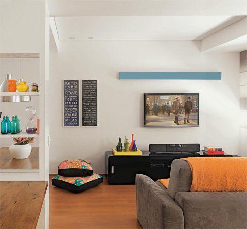 O espaço destinado ao home theater era o terceiro quarto do apartamento – daí as vigas aparentes no teto e na parede da fachada. O sofá com assentos retráteis convida a se esparramar para assistir a filmes. A elegante calha, laqueada de azul, promove uma iluminação suave logo acima da TV, fixada na parede. O rack preto de estilo retro, com cantos levemente arredondados, revela o traço das arquitetas. Há cor por todas as partes: nas almofadas, na manta do sofá, nas obras de arte e nos objetos…