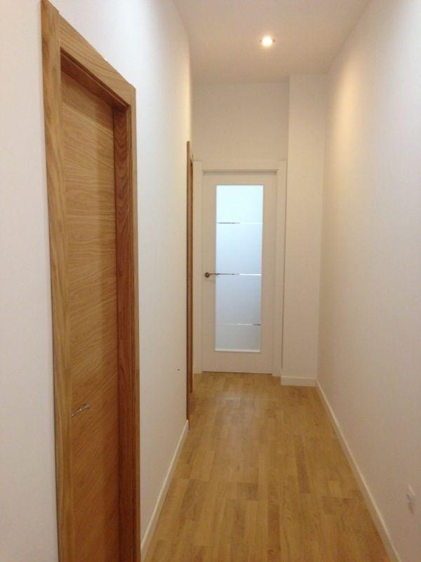 Pasillo con tarima en roble con puerta modelo l62 roble y for Puertas madera y cristal interior