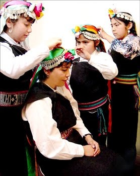 Mapuche ladies helping each other with finishing touches. Also; traditional Mapuche women's clothing reminds me of traditional Pueblo women's clothing!