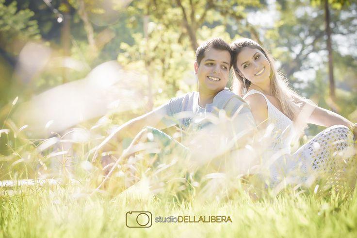 Sessão pre wedding com lindo casal e um sorriso espontâneo, com luz contra deixando um contorno de luz muito bonito, nos noivos e nas gramas a frente do casal, foto feita manhã na praça do bairro monte alegre