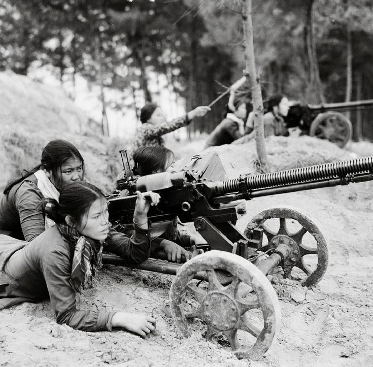 Viet Cong village defense forces lie behind their DSHK-38 machine guns set up along an entrenchment. One of the women in the back appears to be wearing a shirt made from camouflage material.