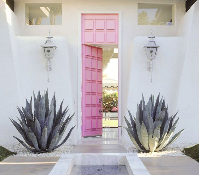 A retro-glam pink door marks the entrance to a Palm Springs vacation home. Interior design by Moises Esquenazi and Associates.