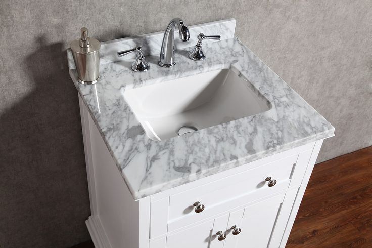 """Virta Yasmine Freestanding 24"""" Vanity in White. A Shaker design with a touch of European style. The vanities are constructed of solid wood with clean and crisp lines. The vanity's sculpted beveled edge plinth with tulip feet showcases its quality and beauty. In a rich white or grey finish with a stunning Carrara marble top and polished chrome hardware."""