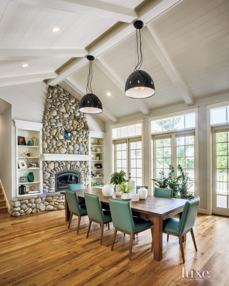 Light fixtures from Schoolhouse Electric & Supply Co. hang in the dining room of a Portland house that designer Garrison Hullinger reimagined for his clients. Turquoise leather chairs by New Pacific Direct surround a table from the owners' existing collection.