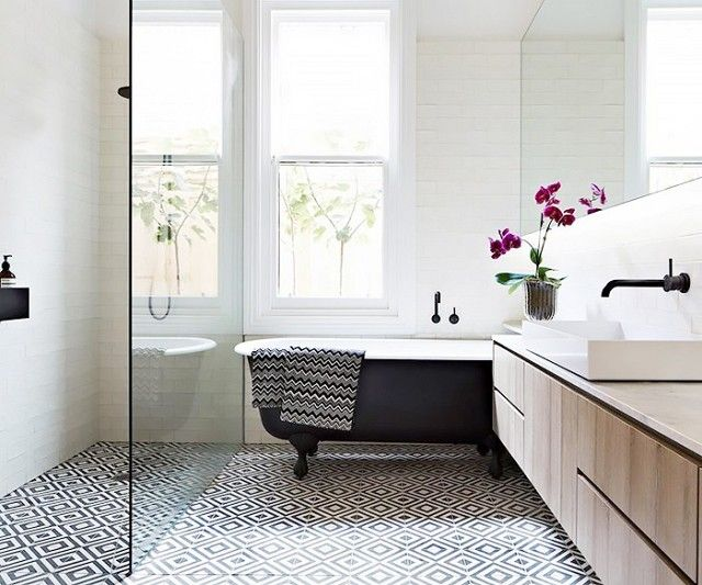 Bathroom with bold geometric tile floors and a clawfoot tub
