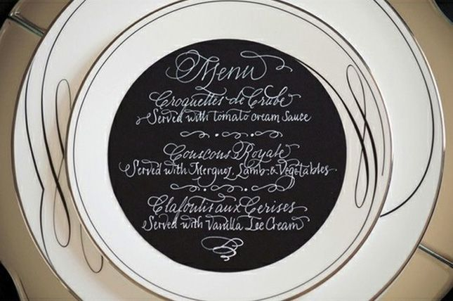 Paint the inside of your chargers with chalkboard paint and write the menu on top.