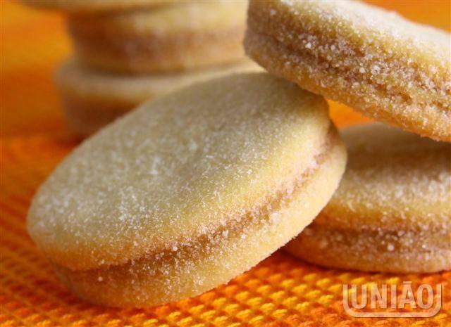 1) Junte o açúcar refinado UNIÃO, a manteiga e a farinha de trigo. Amasse até obter uma massa homogênea.2) Com o rolo, abra a massa e corte em círculos de 4 cm de diâmetro.3) Coloque em uma assadeira sem untar, e asse no forno pré-aquecido, sem deixar corar.Reserve até esfriar.4) Misture o doce de leite com as raspas de laranja. 5) Com esta mistura una os biscoitos de dois em dois e passe-os noaçúcar granulado UNIÃO PREMIUM.6) Mantenha em recipiente bem fechado, para que não amoleçam.