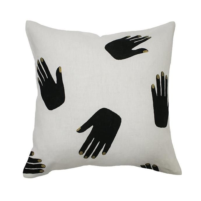white linen cushion patterned with black hand prints with silver nails