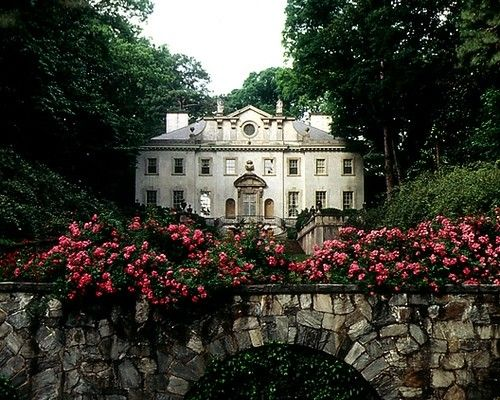 A stunning mansion with a stone arch bridge overflowing with trailing flowers....