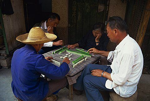 Portrait of a group of four men sitting at a table, playing a game of Mahjong, Yunnan Province, China, Asia
