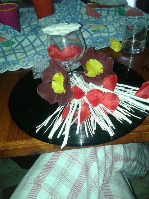 Centro-tavola con disco in vinile e fiori di collant, petali e bastoncini bianchi