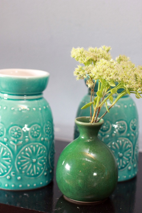 detailfoto van wit-groene bloemen in een groen vaasje