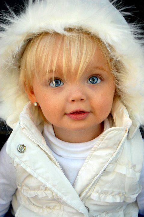 blonde blue eyed baby girl in a white coat