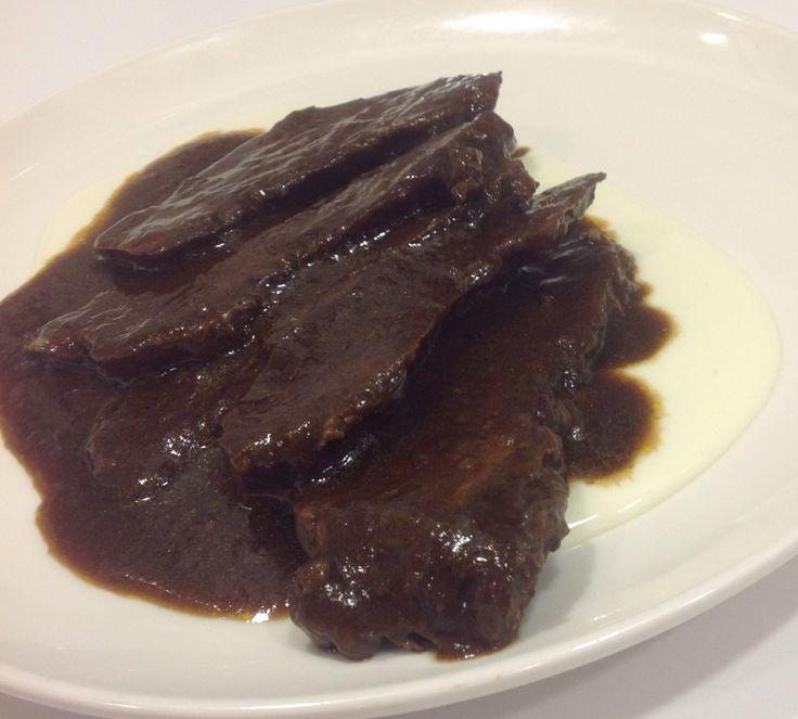 Carrillera de ternera guisada al vino tinto fileteada con crema ligera de patata.