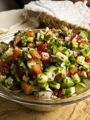 Israelischer Salat › Foodina 1 Zitrone, halbiert 4 Tomaten, gewürfelt 2 Gurken, gewürfelt 1 rote Zwiebel, fein gewürfelt 1 rote Paprika, gewürfelt 1 Knoblauchzehe, zerdrückt 1 grüne Chili, gehackt 1 Prise Zimt 1 TL Sumach Salz Schwarzer Pfeffer, frisch gemahlen 3 EL Olivenöl 2-3 EL Blattpetersilie, gehackt 2-3 EL Koriandergrün, gehackt 2-3 EL Minze, gehackt