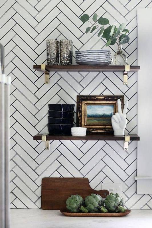 Proof that a solid herringbone pattern looks just as good on a backsplash as it would on the floor. Complement the look with wooden shelves reinforced with brass brackets. This refreshing take maintains the timeless elegance of a black and white color scheme, yet still manages to bring in a modern update in the form of the pattern.