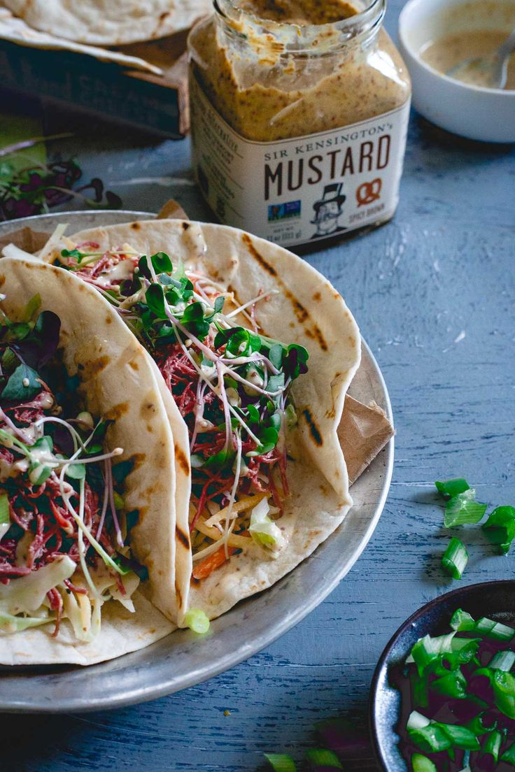These corned beef tacos are served with a creamy spicy mustard sauce, a simple cabbage carrot slaw and topped with microgreens. Celebrate St. Patrick's Day with a Mexican twist!   @sirkensington #sponsored